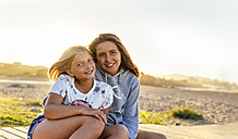 Portrait of two smiling girls sitting on boardwalk - MGOF03665