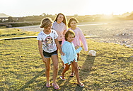 Four girls playing outdoors at sunset girls on boardwalk - MGOF03674