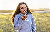 Portrait of smiling girl using cell phone outdoors - MGOF03680