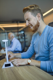 Happy man in office with model wind turbine - ZEDF00924