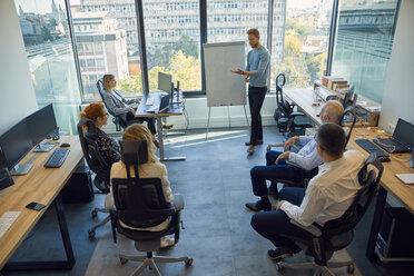 Man leading a presentation at flip chart in office - ZEDF00936