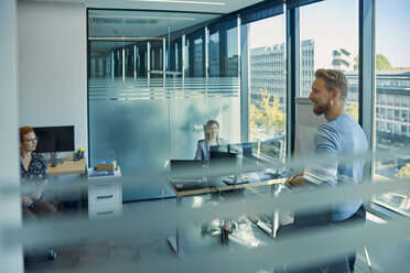 Smiling man leading a presentation in office - ZEDF00939