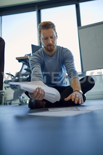 Businessman organising papers on the floor in office - ZEDF00948