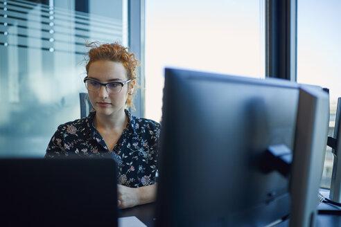 Businesswoman working at desk in office - ZEDF00966