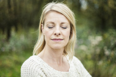 Portrait of blond woman with eyes closed outdoors - MOEF00248