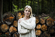Portrait of blond woman at stack of logs in the forest - MOEF00254