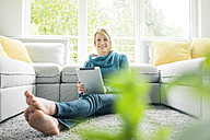 Portrait of happy woman with tablet in living room - MOEF00272