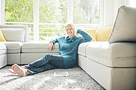 Portrait of smiling woman relaxing in living room - MOEF00275