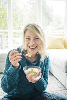 Portrait of happy woman eating fruit muesli in living room - MOEF00278