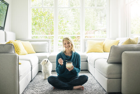 Portrait of happy woman with dog eating fruit yoghurt in living room - MOEF00281