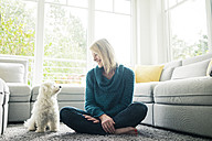 Smiling woman looking at her dog in living room - MOEF00284