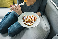 Close-up of woman sitting on couch eating pancakes - MOEF00287