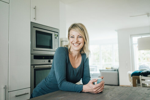 Portrait of smiling blond woman at home - MOEF00290