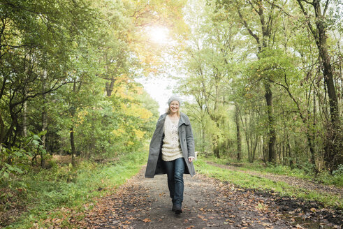 Portrait of happy woman walking in the forest in autumn - MOEF00293