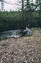 Man sitting at riverside with waders - VPIF00237