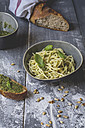 Homemade basil pesto, spaghetti in a bowl, rye baguette on wood - ODF01561