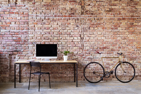 Workspace and bicycle at brick wall in office - HAPF02339