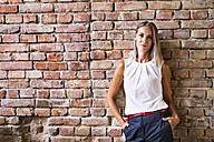 Portrait of young woman at brick wall in office - HAPF02342