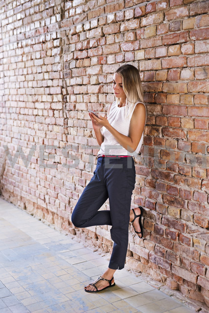 Businesswoman using cell phone at brick wall - HAPF02345