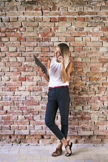 Businesswoman holding clipboard and using cell phone at brick wall in office - HAPF02348