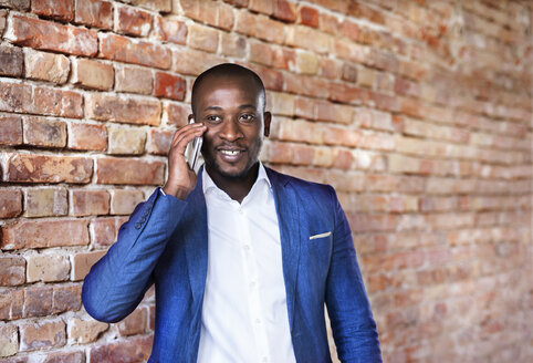 Businessman using cell phone at brick wall - HAPF02351