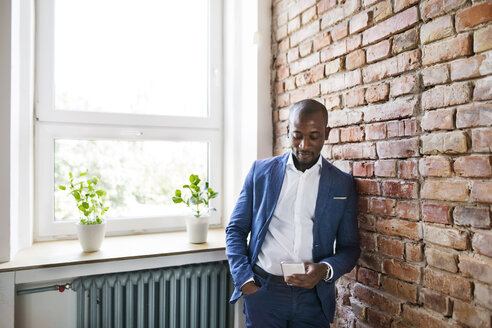 Businessman using cell phone at brick wall by the window - HAPF02354
