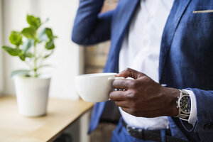 Close-up of businessman with cup of coffee at the window - HAPF02357
