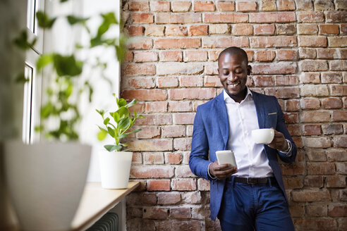 Smiling businessman using cell phone at brick wall by the window - HAPF02360