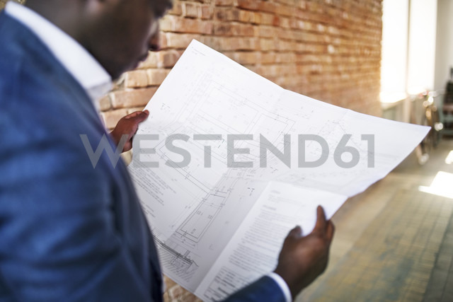 Businessman studying construction plan at brick wall - HAPF02366