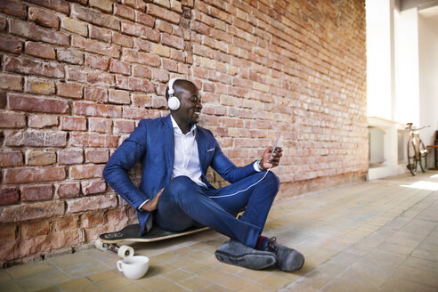 Smiling businessman sitting on longboard listening to music with headphones - HAPF02369