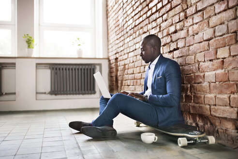 Businessman sitting on longboard at brick wall using laptop - HAPF02375