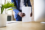 Close-up of businessman with papers at desk in office - HAPF02381
