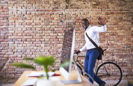 Smiling businessman pushing bicycle in office and waving - HAPF02393