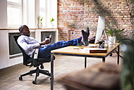 Businessman sitting in office with feet on desk checking cell phone - HAPF02396