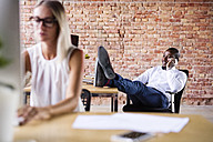 Businessman on the phone in office with colleague working in foreground - HAPF02399