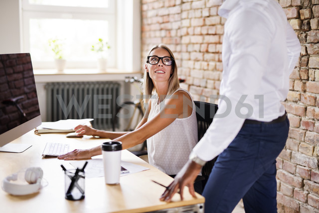 Two colleagues working together at desk in office - HAPF02405