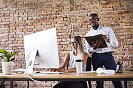 Businessman behind woman working at desk in office - HAPF02408