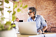 Businessman using laptop in office with colleague in background - HAPF02423