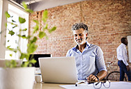 Smiling businessman using laptop in office with colleague in background - HAPF02426