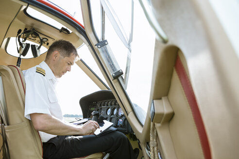 Pilot using tablet in cockpit of a helicopter - OJF00197