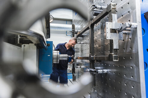 Man working on machine in industrial factory - DIGF03107