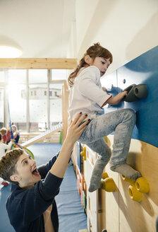 Pre-school teacher helping little girl climbing up a wall - MFF04053
