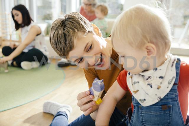 Pre-school teacher playing with toddler in kindergarten - MFF04068 - Mareen Fischinger/Westend61
