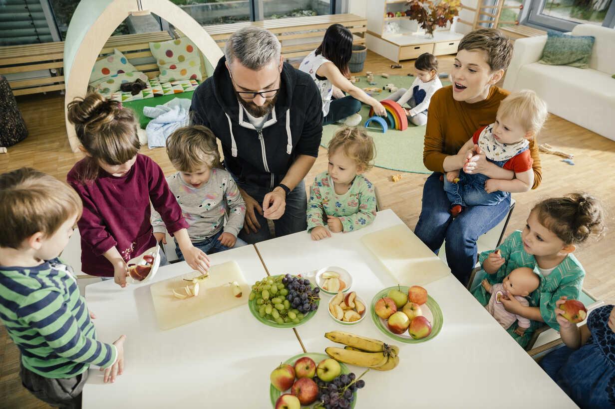 Group of children and teachers preparing fruit in kindergarten - MFF04071 - Mareen Fischinger/Westend61