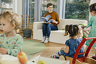 Pre-school teacher with book looking at children in kindergarten - MFF04074