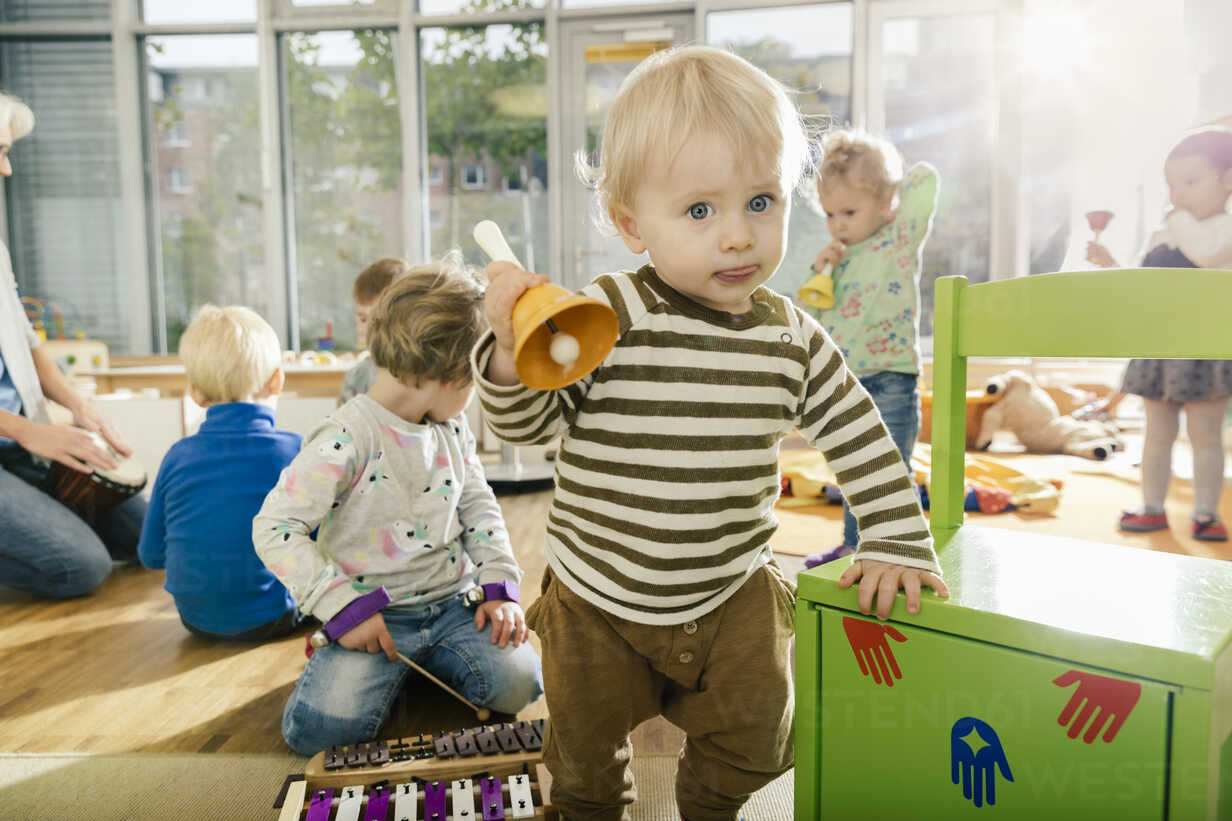 Toddler ringing a bell in music room of a kindergarten - MFF04080 - Mareen Fischinger/Westend61