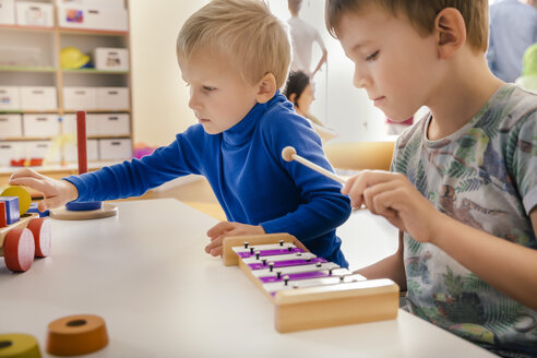 Two boys playing with musical instruments and toys in kindergarten - MFF04089