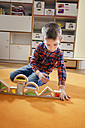 Boy lining up wooden toy shapes on carpet in kindergarten - MFF04095