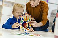 Child and pre-school teacher building a bird table in kindergarten - MFF04131