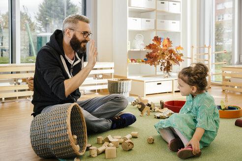 Pre-school teacher playing with girl in kindergarten - MFF04140